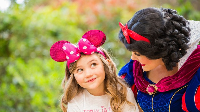 A Snow White character interacts with a little girl at a Disney park.