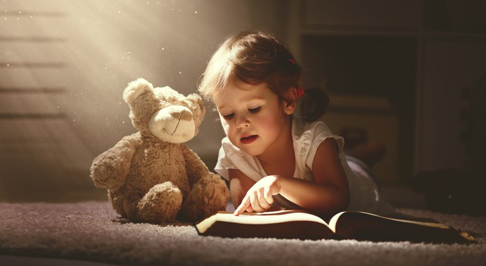 A young girl reading a book next to her teddy bear.