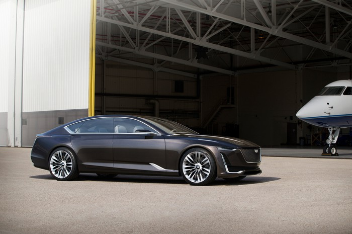 The Cadillac Escala show car, a long black luxury sedan, in an airport hangar