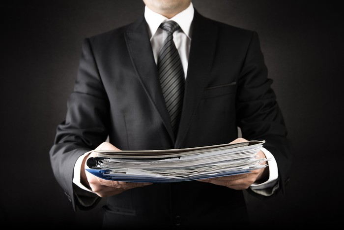 Man wearing a suit holding a pile of documents