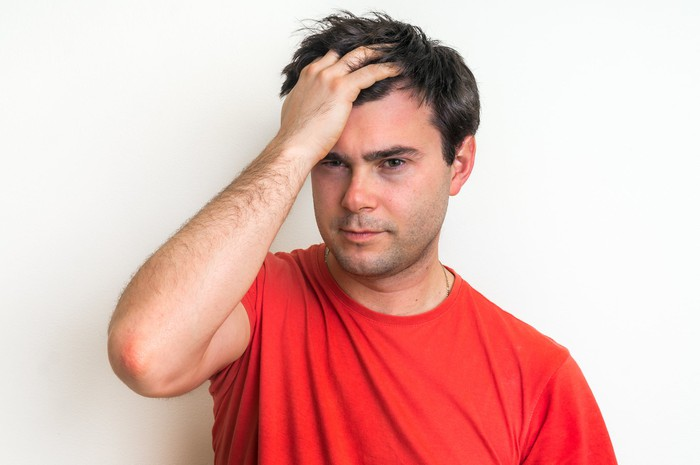 Man smacking his own head after making a mistake