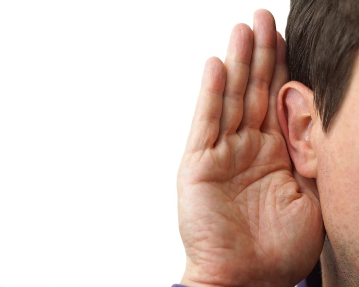 Businessman with hand cupped on ear to listen