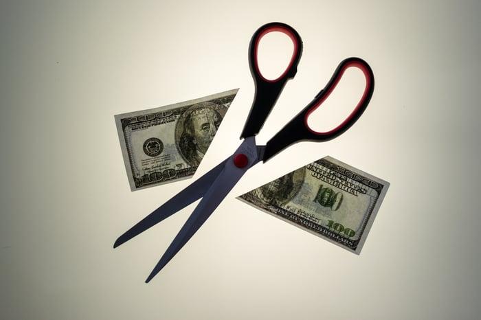 scissors cutting bill in half