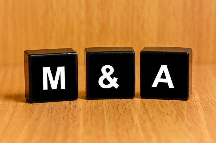 "Black blocks that spell out ""M&A"" on wood background."
