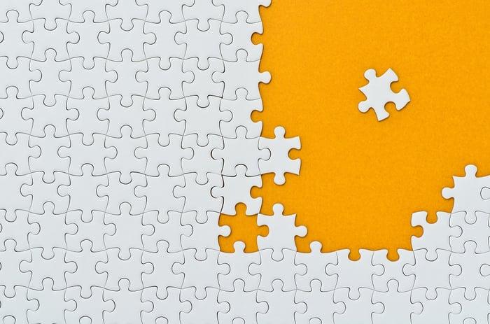 Photo of white puzzle pieces on orange background.