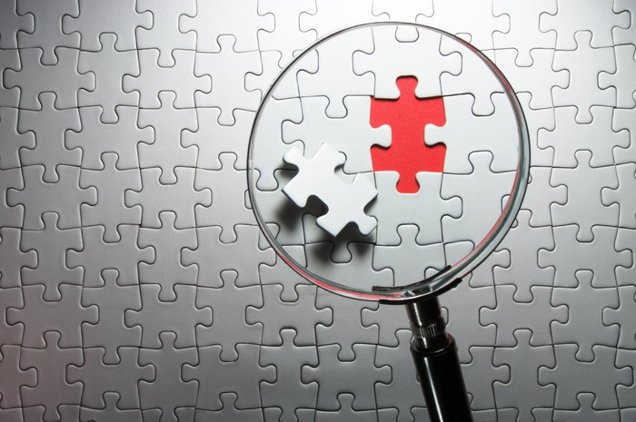 Missing jigsaw puzzle piece under magnifying glass