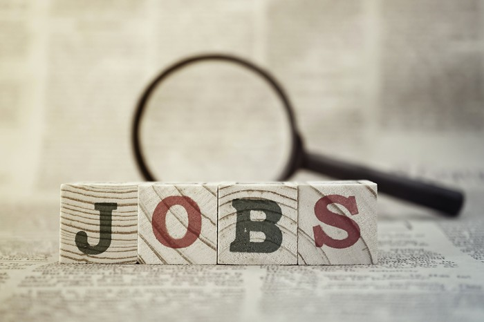 Jobs spelled out in wooden blocks with magnifying glass