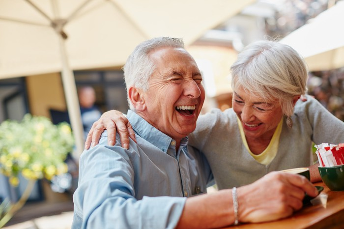 A retired husband and wife laughing.