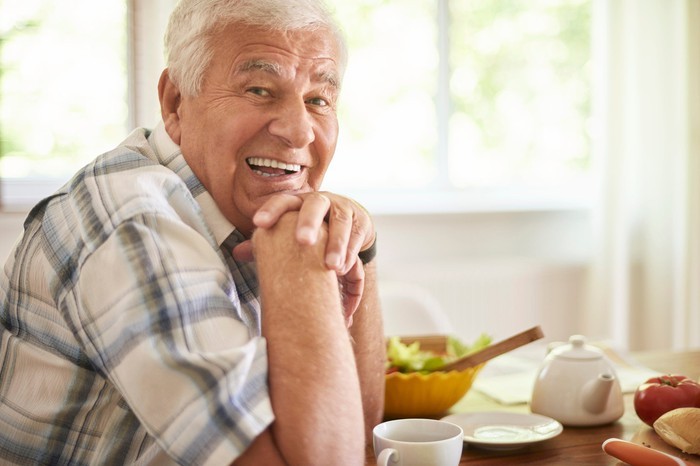 An elderly man smiling while sitting at his breakfast table.
