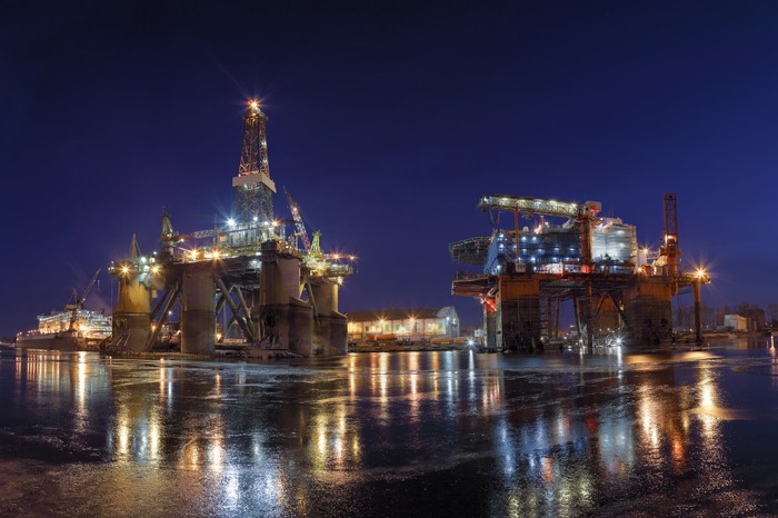 idle offshore rigs in a shipyard at night