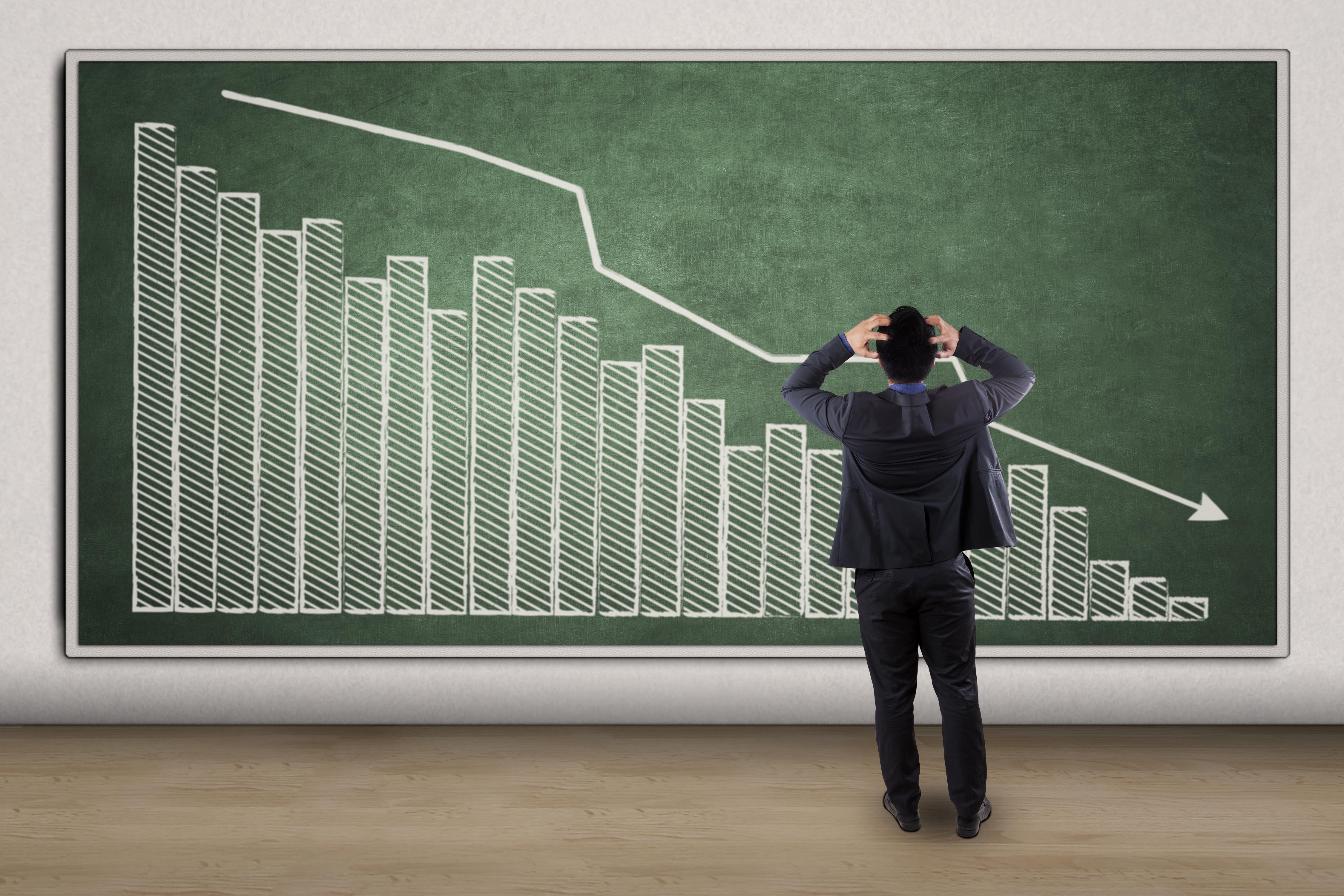 An arrow following a downward trending graph on a chalkboard.