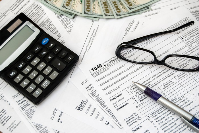 Cash, a pen, glasses, and a calculator strewn across a pile of tax forms.