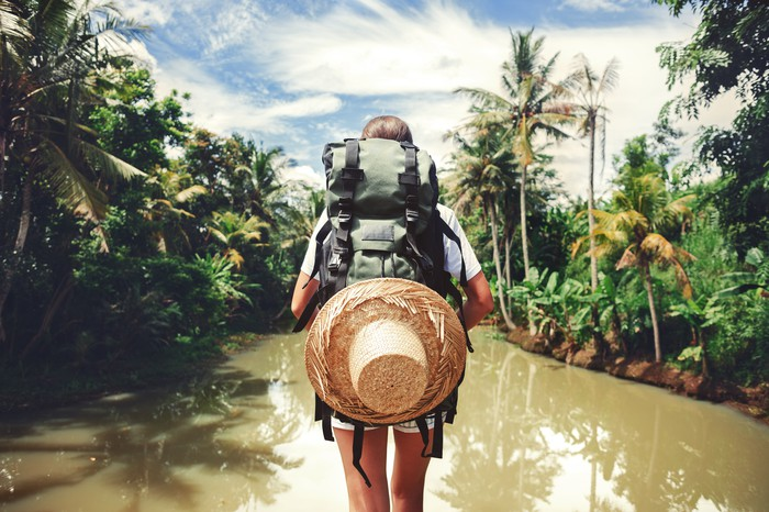 A woman traveler carrying a backpack walking through a muddy river
