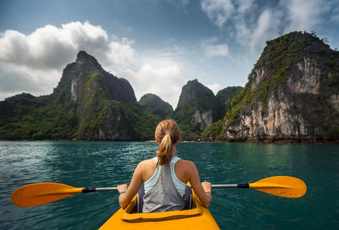 Woman in a yellow kayak overlooking a beautiful island.