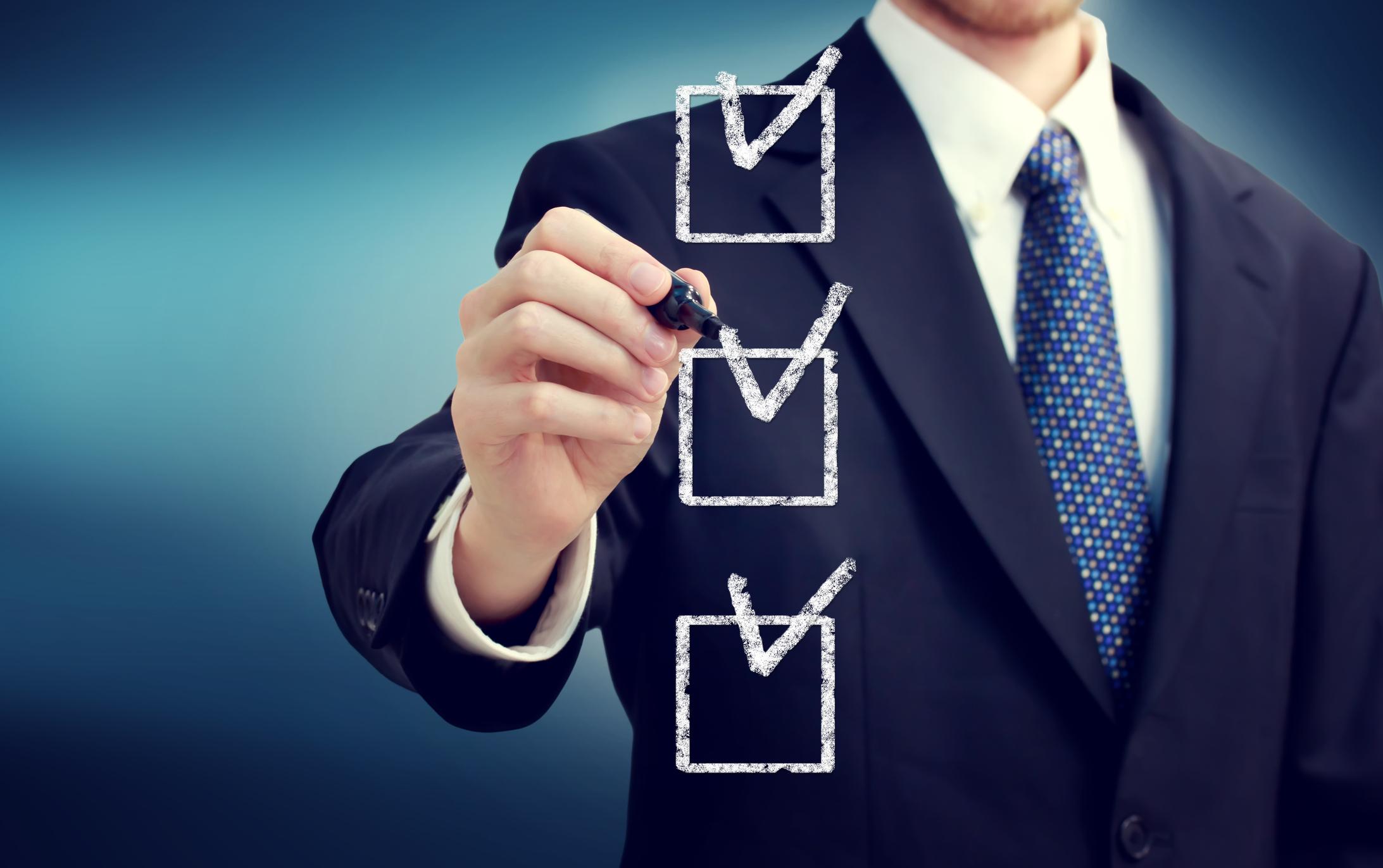 A businessman ticks off boxes on a checklist.