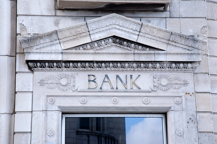"""Front door of a bank with the word """"bank"""" above the entrance."""