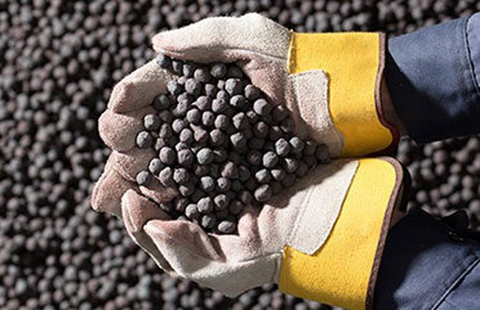 Hands holding iron ore pellets