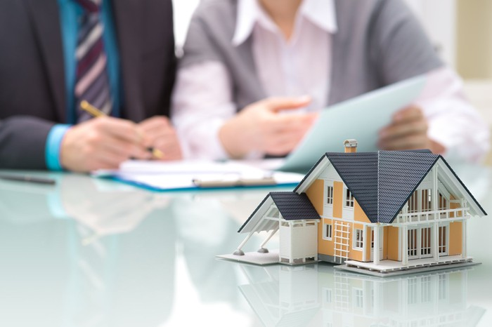 Two people signing documents, behind a model of a house on a table.