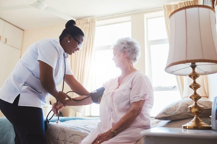 Nurse examining elderly woman in senior housing facility.