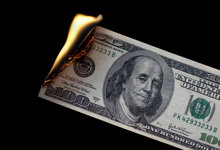 $100 bill on fire.