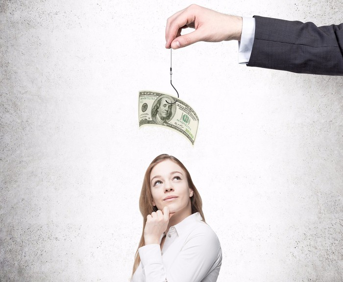 Standing woman seems to be contemplating an arm holding up a fishing hook with a $100 bill on it above her