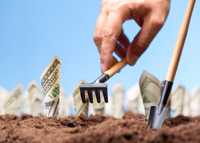 A hand using tiny gardening tools to plant money in the soil.