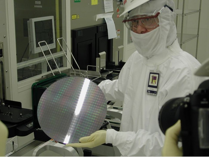 Intel lab tech holding a silicon wafer.