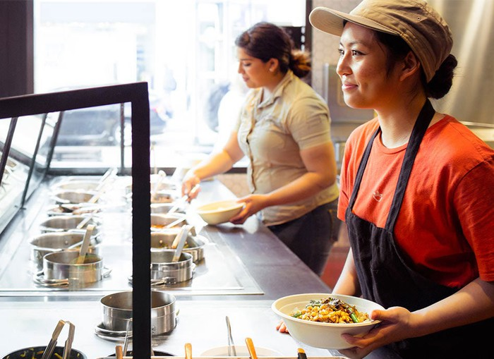 Employees at ShopHouse on the food assembly line.