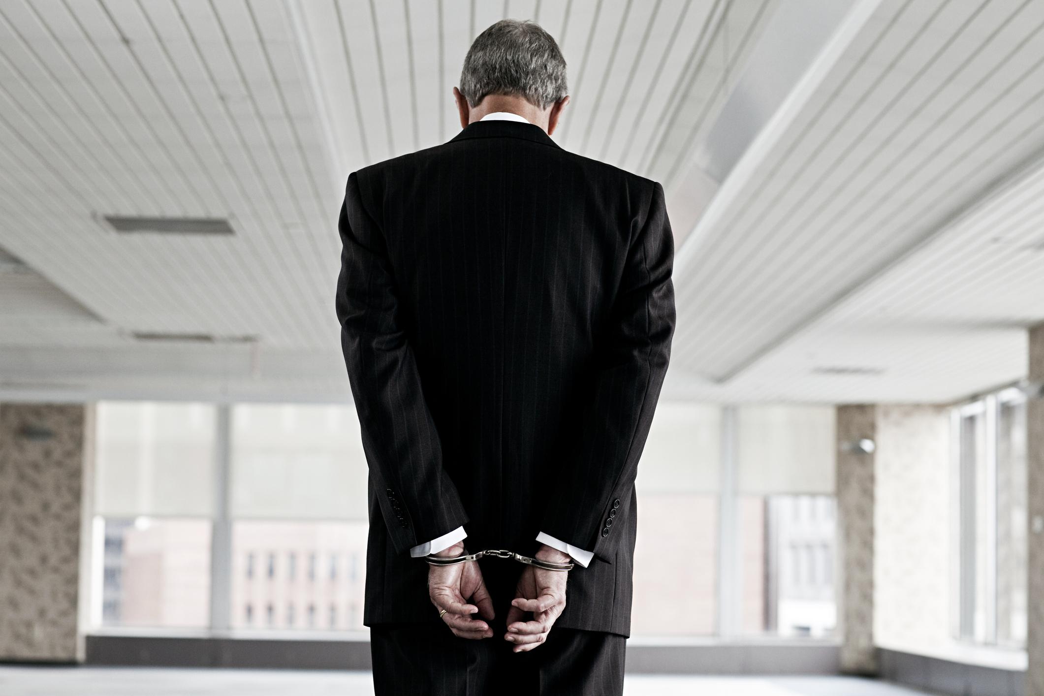 A businessman in handcuffs.