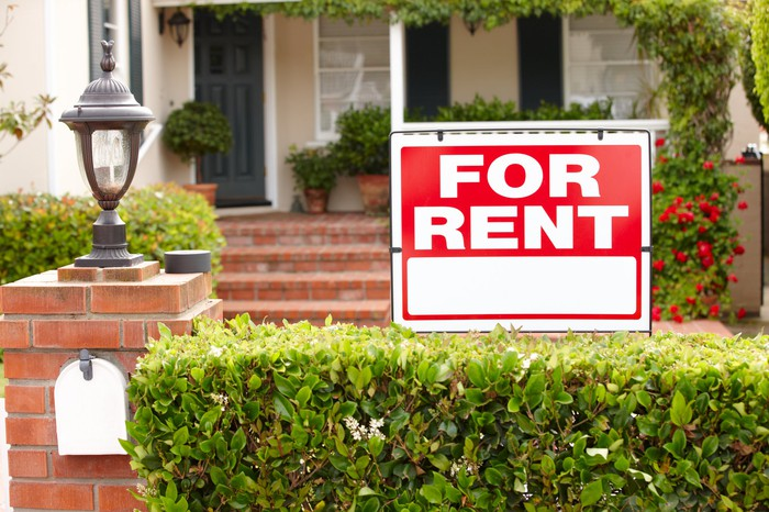 """House with a """"for rent"""" sign in the front yard."""