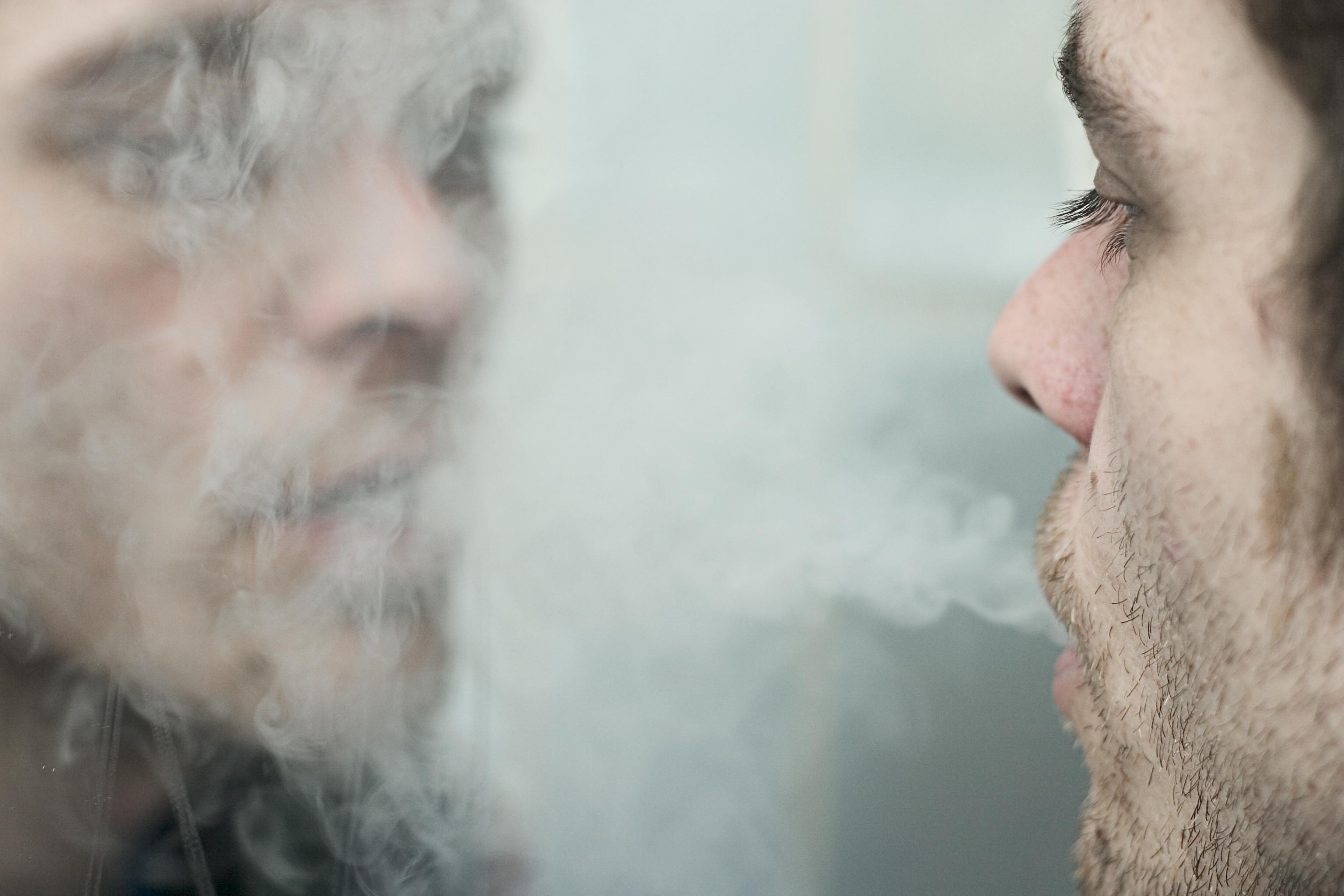 Man blowing smoke into a mirror.