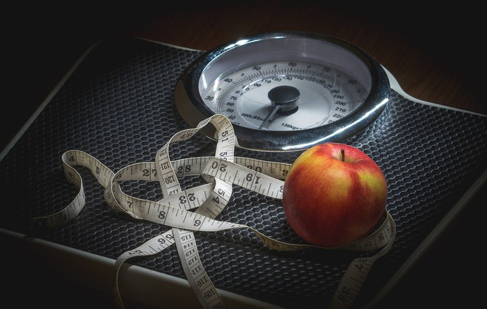 A scale with an apple and a tape measure on top of it.