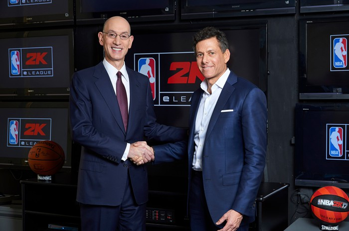 """Take-Two CEO Strauss Zelnick shakes hands with NBA Commissioner Adam Silver in front of a screen that says """"NBA 2K."""""""