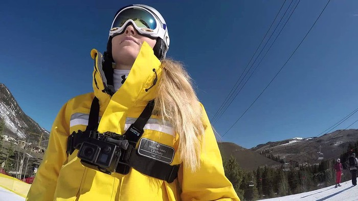 A Vail resorts ski patrol member in a bright yellow jacket looking up a mountain.