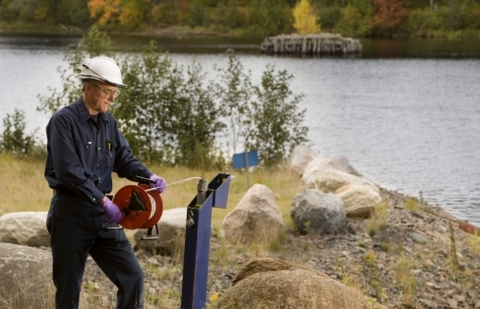 A Cameco employee sampling water.