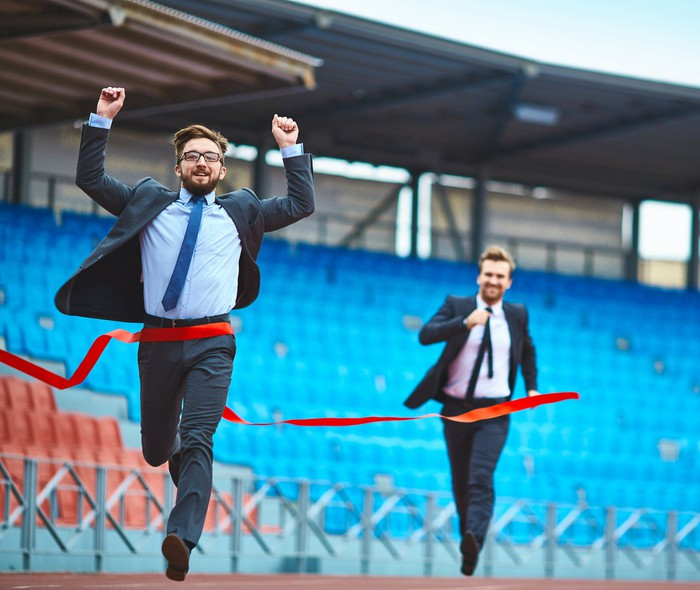 Two men in suits racing toward the finish line, with one raising his arms in victory.