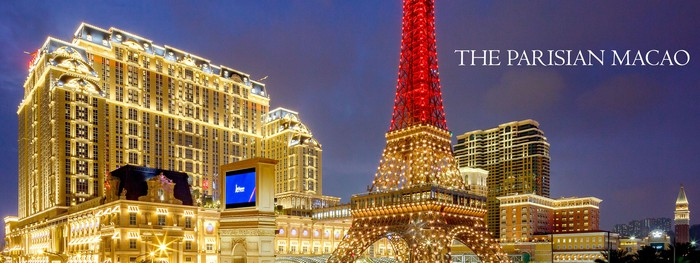 """Las Vegas Sands """"Parisian"""" resort lit up in gold, with the famous 50% scale eiffel tower in red."""