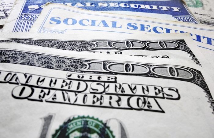 Social Security card with hundred dollar bills