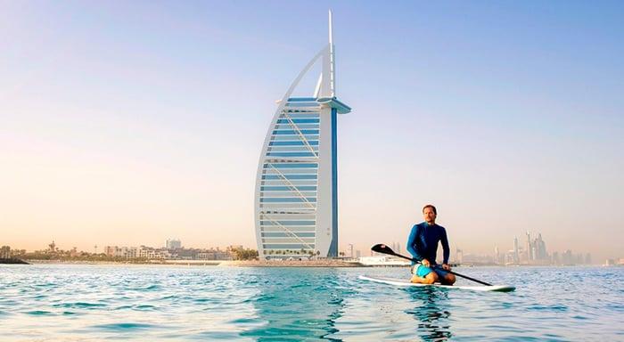 A man rides a paddle board on a lake in Dubai.