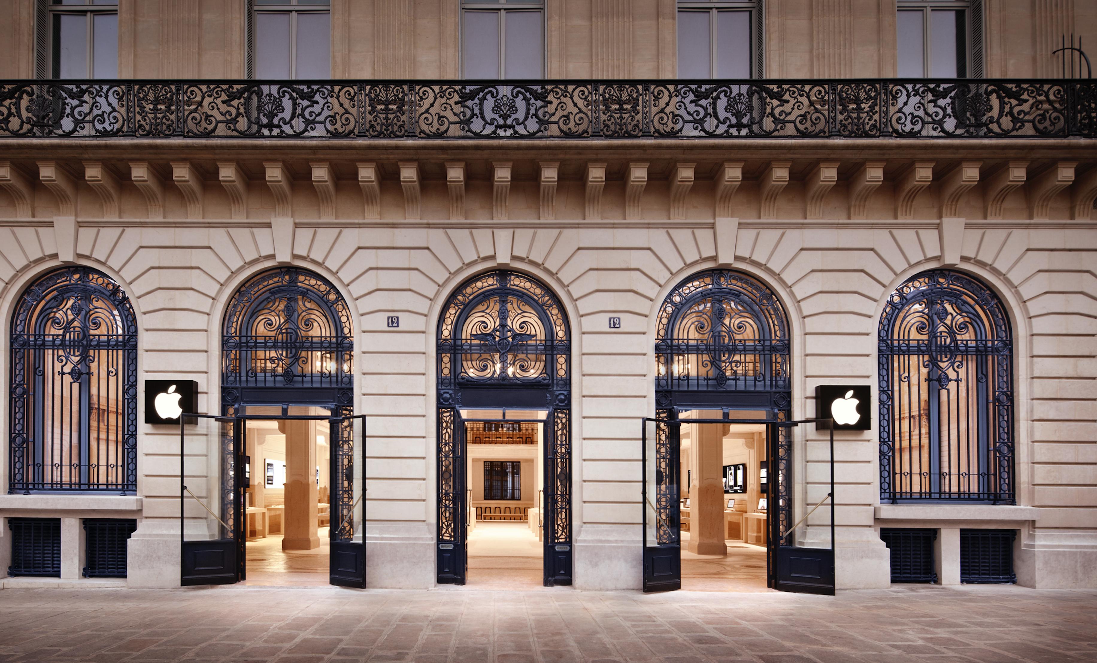 Apple storefront in Paris with black Apple logo in window display.