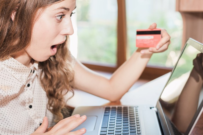 A young woman holding a credit card and looking at her laptop screen in utter shock.