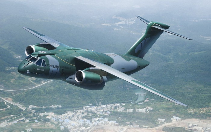 A KC-390 military tanker flying over a forest