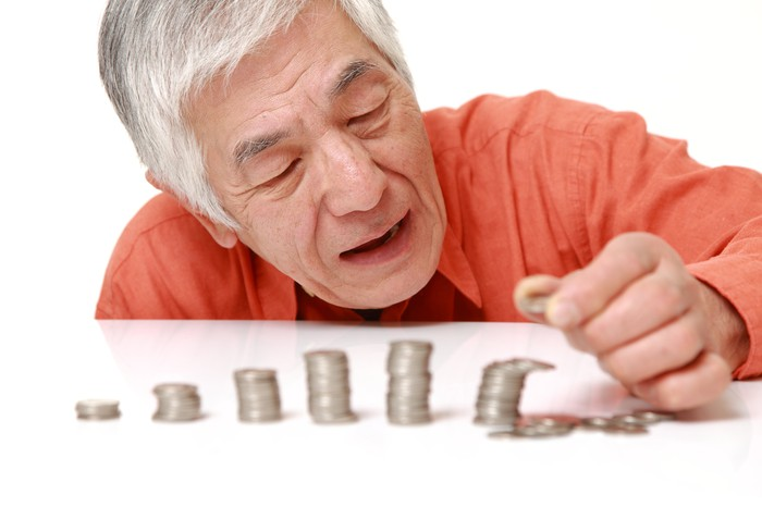 A man stacking coins in taller piles from left to right.