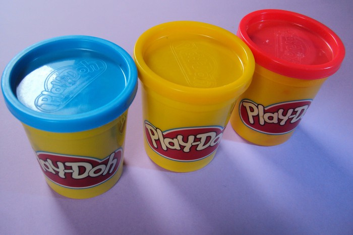 Three containers of Play-Doh on a table.