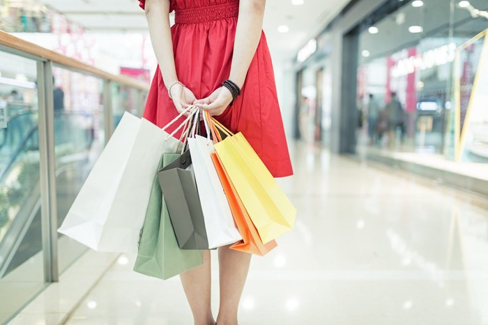 Young woman in red dress carrying shopping bags in upscale shopping mall.