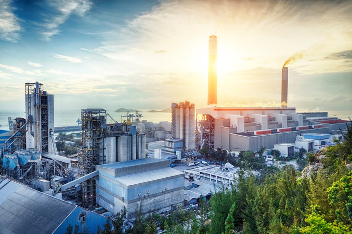 A power plant by the water shown at sunrise.