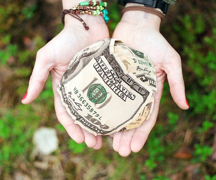 A hand holding out a ball of money, representing charitable giving.