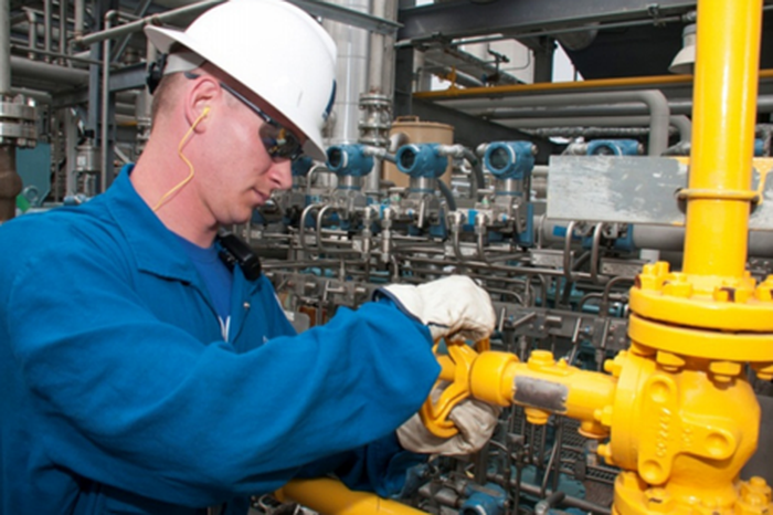 An Enterprise Products Partners employee turning a yellow valve.