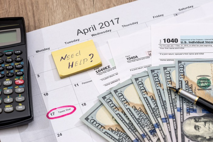 "Tax forms, cash, a pen, and a calculator sitting on a calendar with Tax Day circled, and a sticky note with the words ""need help?"""