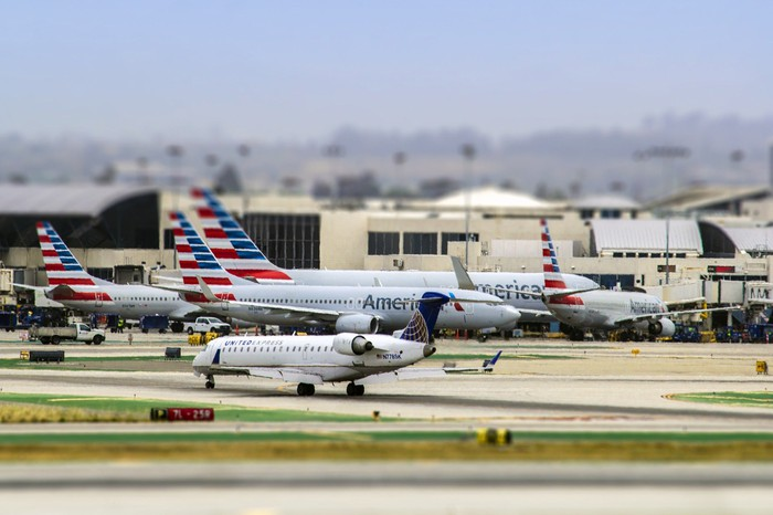 A United Airlines regional jet taxis in the foreground, with American Airlines jets in the background